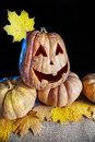 Halloween pumpkin with yellow maple leave at black background Royalty Free Stock Photos