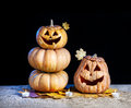 Halloween pumpkins and candles nearby on the dry yellow leaves at black background Stock Image