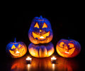 Halloween pumpkins glowing inside scary with eyes at black background Stock Image