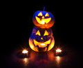Halloween pumpkins glowing inside scary with eyes at black background Stock Photos
