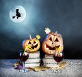 Halloween pumpkins and witch drinking wine on the heap of books silhouette on the broom flying near the full moon at dark Stock Images