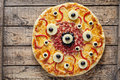Halloween scary food monster pizza with eyes on vintage wooden table