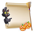 Halloween scroll sign a with black cat pointing at the and carved pumpkins and witch s broom stick Royalty Free Stock Images