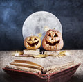 Halloween story pumpkins reading old book at full moon and dark sky background Stock Photo
