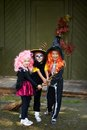 Halloween team portrait of three girls with broom looking at camera outside Royalty Free Stock Photography