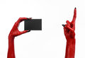 Halloween theme: Red devil hand with black nails holding a blank black card on a white background Royalty Free Stock Photo