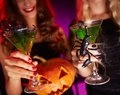 Halloween toast photo of carved pumpkin and cocktails with scorpions held by females Stock Photography