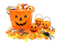 Halloween treats jack o lantern pails with pile of candy over white Royalty Free Stock Images