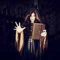 Halloween witch holding magical book of spells making magic beautiful young wearing vintage gothic dress with hood in old leather Stock Photos