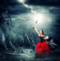 Halloween witch making magic and controls the weather shoots lightning into the sky from the magical staves Stock Photos
