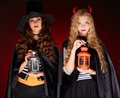 Halloween witches portrait of two girls with lanterns looking at camera Stock Image