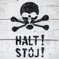 Halt stoj stop sign in german and polish with a painted skull Royalty Free Stock Photo