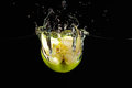 Halved green apple falling into water with splash Royalty Free Stock Photo