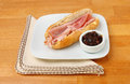 Ham baguette with pickle on a plate with a serviette on a wooden table Stock Photos