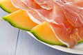 Ham and cantaloupe melon on the gray table Stock Photography