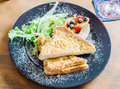 Ham cheese French toast serve with grilled sausage, salad, blueberry, strawberry and topping with icing sugar Royalty Free Stock Photo