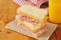 Ham and cheese sandwich a on a rustic wooden table with orange juice Royalty Free Stock Photography