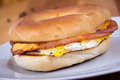Ham egg and cheese breakfast sandwich on a bagel over wood table Royalty Free Stock Photo