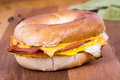 Ham egg and cheese breakfast sandwich on a bagel over wood table Royalty Free Stock Images