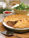 Ham and meat pie with homemade ketchup green salad with serving spatula on side decorations in the background Royalty Free Stock Photo