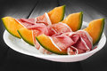 Ham and melon on the white dish Stock Photos
