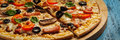 Ham pizza close up letterbox panorama of with capsicum mushrooms olives and basil leaves on wooden board on blue table Stock Photo