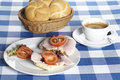 Ham rolls and a cup of coffee plate with trimming tomato slices salad basket bread on table the table is Stock Image