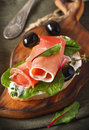 Ham sandwich with olives and chard on an old wooden board Stock Image