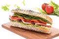 Ham and vegetable submarine sandwich on bamboo cutting board Stock Image