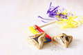 Hamantaschen cookies or hamans ears for purim celebration and noisemaker over textured wooden board Stock Image