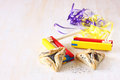 Hamantaschen cookies or hamans ears for purim celebration and noisemaker over textured wooden board Stock Photo