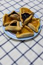 stock image of  Hamantash Purim Blueberry and apricot jam cookies on colored plate on tablecloth with blue squares background