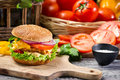Hamburger chicken tomato vegetables old wooden table Royalty Free Stock Photography