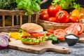 Hamburger with chicken tomato and vegetables on old wooden table Stock Photo