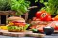 Hamburger chicken vegetables fresh herbs old wooden table Stock Photography