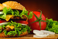 Hamburger closeup and vegetables still life with tomato onions lettuce Royalty Free Stock Photos