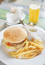 Hamburger with french fries and sauce on the table in cafe Royalty Free Stock Photo
