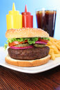 Hamburger with french fries, soda and condiments Royalty Free Stock Photography