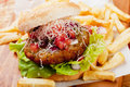 Hamburger with grated cheese classic tomato and served french fries Stock Image