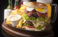 Hamburger large abundant and tasty with french fries Royalty Free Stock Images