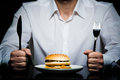 Hamburger on a plate in front of a man Royalty Free Stock Photo