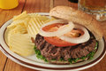 Hamburger with potato chips a on a whole wheat bun and beer Royalty Free Stock Photography
