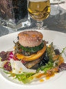 Hamburger on some vegetables served a plate it s a vertical picture Royalty Free Stock Photos