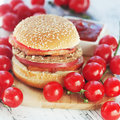 Hamburger and tomatoes on wooden background Stock Image