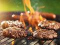 Hamburgers and hotdogs cooking on flaming grill with slight lens flare Stock Photography