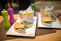 Hamburgers served with fries.Colorful.Hamburger with beef meet, vegetables, ketchup and chips on plate.Unhealthy,fatty food Royalty Free Stock Photo