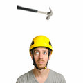 Hammer and hard hat a falling on the head of a bearded man with a yellow Stock Photos