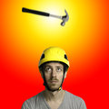 Hammer and hard hat a falling on the head of a bearded man with a yellow with yellow red background Royalty Free Stock Image