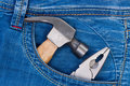 Hammer and pliers in pocket jeans. Royalty Free Stock Photos