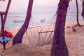 Hammock on the beach hanging between palm trees Stock Photo